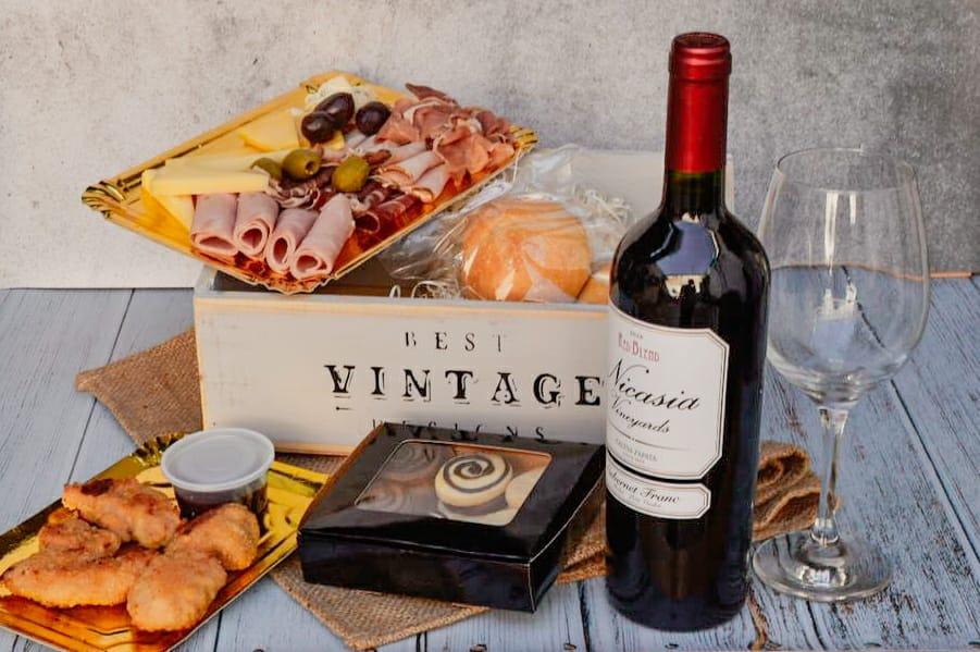 Cajón de madera con vino y picada